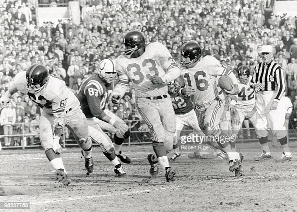 Frank Gifford of the New York Giants carries the ball as Mel Triplett and Darrell Dess block against Don Joyce of the Baltimore Colts during the 1959...