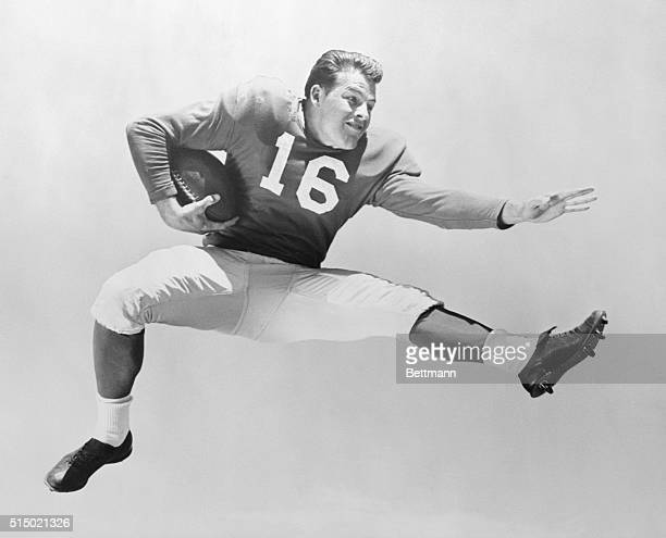 Frank Gifford of the New York Giants football team leaping, and holding football under right arm. .