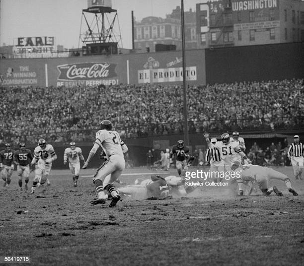 Frank Gifford, of the New York Giants, is sacked from behind by Chuck Bednarik, of the Philadelphia Eagles, to stop the last chance the Giants had of...