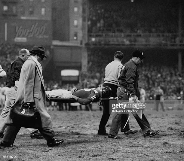 Frank Gifford, of the New York Giants, is taken from the field after being hit by Chuck Bednarik, of the Philadelphia Eagles, to stop the last chance...
