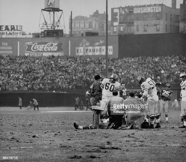 Frank Gifford, of the New York Giants, lays on the field after being hit by Chuck Bednarik, of the Philadelphia Eagles, to stop the last chance the...