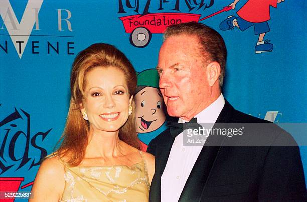 Frank Gifford with his wife Kathie Lee Gifford in front of a cartoon backdrop; circa 1990; New York.
