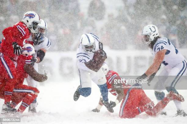 Frank Gore of the Indianapolis Colts runs the ball as Jerry Hughes of the Buffalo Bills attempts to tackle him during the December 10 2017 at New Era...
