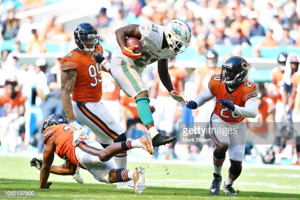Frank Gore of the Miami Dolphins jumps over the defense of Adrian Amos of the Chicago Bears in the second half of the game at Hard Rock Stadium on...