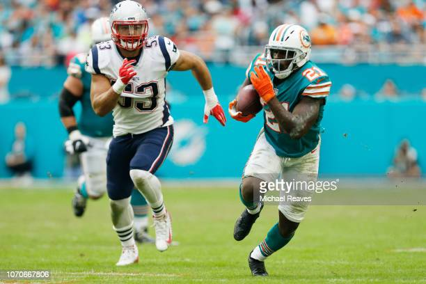 Frank Gore of the Miami Dolphins rushes and avoids the tackle of Kyle Van Noy of the New England Patriots during the second half at Hard Rock Stadium...
