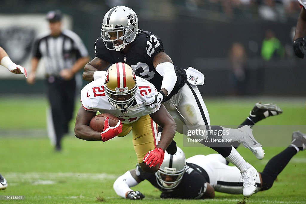 Frank Gore #21 of the San Francisco 49ers catches air from the tackle of Tarell Brown #23 of the Oakland Raiders in the first quarter at O.co Coliseum on December 7, 2014 in Oakland, California.