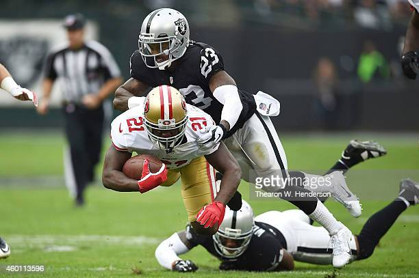 Frank Gore of the San Francisco 49ers catches air from the tackle of Tarell Brown of the Oakland Raiders in the first quarter at Oco Coliseum on...