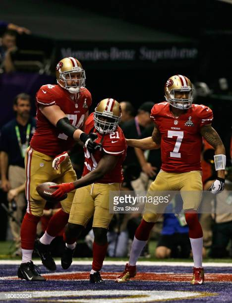 Frank Gore of the San Francisco 49ers celebrates with teammates Colin Kaepernick and Joe Staley after scoring a touchdown in the third quarter...