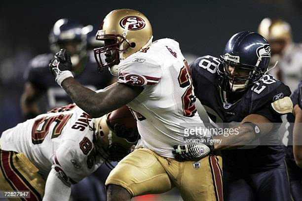 Frank Gore of the San Francisco 49ers runs with the ball against Michael Boulware of the Seattle Seahawks on December 14 2006 at Qwest Field in...