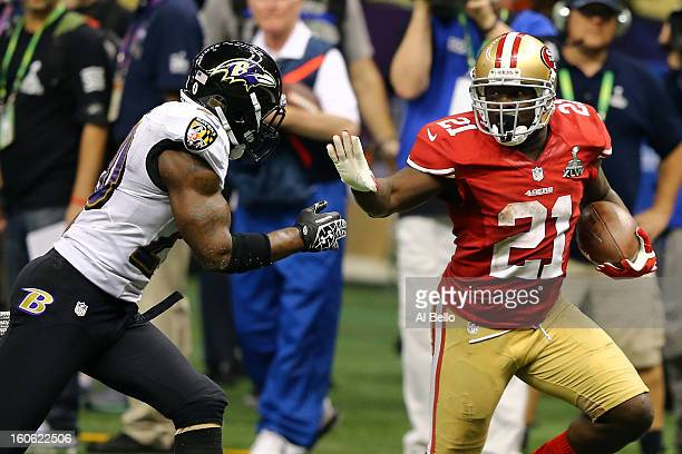 Frank Gore of the San Francisco 49ers runs with the ball before stiff-arming Ed Reed of the Baltimore Ravens during Super Bowl XLVII at the...