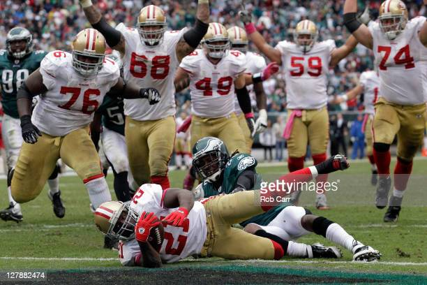 Frank Gore of the San Francisco 49ers scores a touchdown while being tackled by Asante Samuel of the Philadelphia Eagles during the second half at...