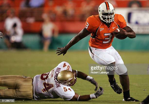 Frank Gore of the University of Miami Hurricanes runs with the ball as AJ Nicholson of the Florida State Seminoles tries to block him in the first...