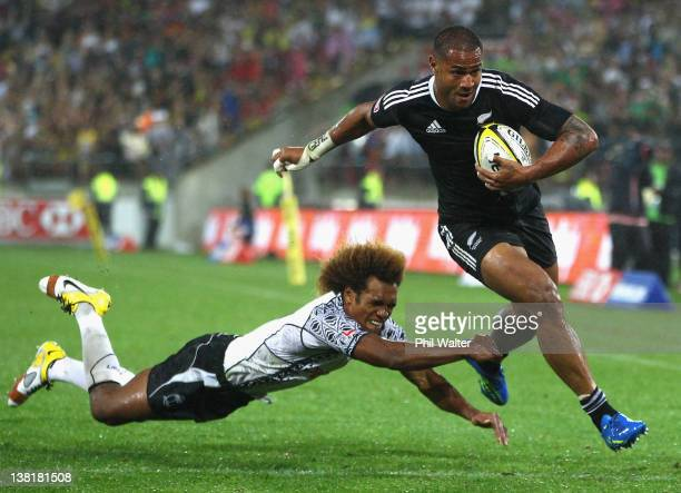 Frank Halai of New Zealand breaks through the tackle of Osea Kolinisau of Fiji to score a try during the Cup Final on day two of the Wellington...