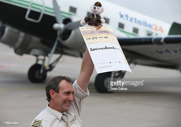 Frank Hellberg, Chairman of the Rosinenbomber Verien, or Candy Bomber Association, holds up the official Candy Bomber teddy bear after his arrival in...