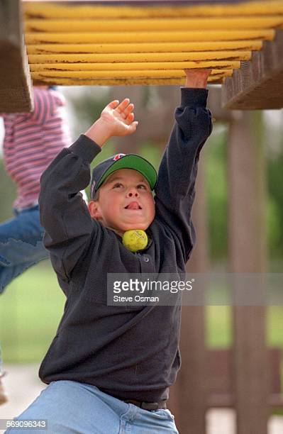 Frank Herrera 11 of Oxnard makes his way across the monkey bars at Sierra Linda Park in Oxnard with tongue out and tennis ball under chin