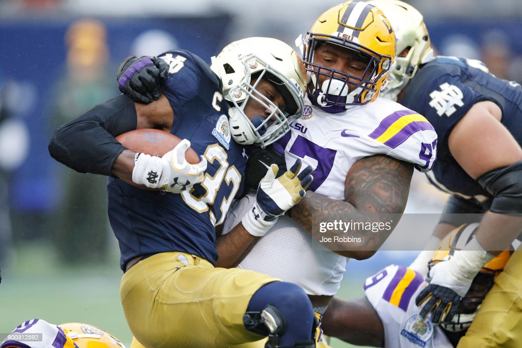 Frank Herron #97 of the LSU Tigers tackles Josh Adams #33 of the Notre Dame Fighting Irish in the first half of the Citrus Bowl on January 1, 2018 in Orlando, Florida.