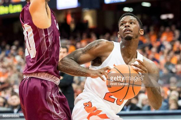 Frank Howard of the Syracuse Orange loses the ball while drives to the basket against Francisco Amiel of the Colgate Raiders during the first half at...