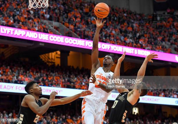 Frank Howard of the Syracuse Orange shoots the ball between Terrence Thompson and Mitchell Wilbekin of the Wake Forest Demon Deacons during the...