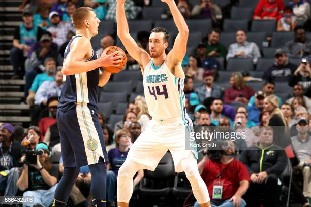 Frank Kaminsky of the Charlotte Hornets defends Nikola Jokic of the Denver Nuggets on October 25 2017 at Spectrum Center in Charlotte North Carolina...