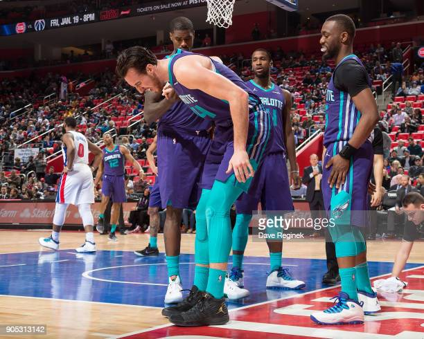 Frank Kaminsky of the Charlotte Hornets is helped up after twisting his ankle in the fourth quarter against the Detroit Pistons during the an NBA...