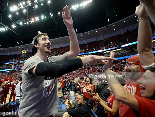 Frank Kaminsky of the Wisconsin Badgers celebrates with fans defeating the Arizona Wildcats 6463 in overtime during the West Regional Final of the...