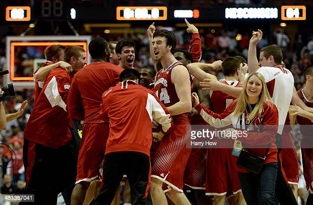 Frank Kaminsky of the Wisconsin Badgers celebrates with teammates after defeating the Arizona Wildcats 6463 in overtime during the West Regional...