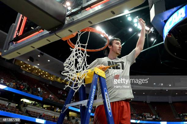 Frank Kaminsky of the Wisconsin Badgers cuts down the net after defeating the Arizona Wildcats 6463 in overtime during the West Regional Final of the...