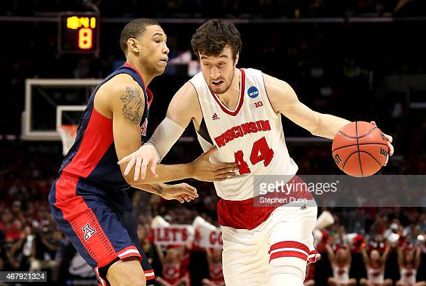 Frank Kaminsky of the Wisconsin Badgers drives on Brandon Ashley of the Arizona Wildcats in the first half during the West Regional Final of the 2015...