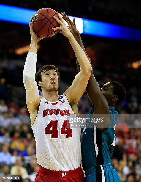 Frank Kaminsky of the Wisconsin Badgers goes up against Tristian Curtis of the Coastal Carolina Chanticleers in the first half during the second...