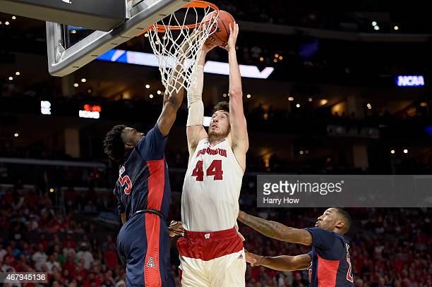 Frank Kaminsky of the Wisconsin Badgers goes up for a dunk against Stanley Johnson of the Arizona Wildcats in the second half during the West...