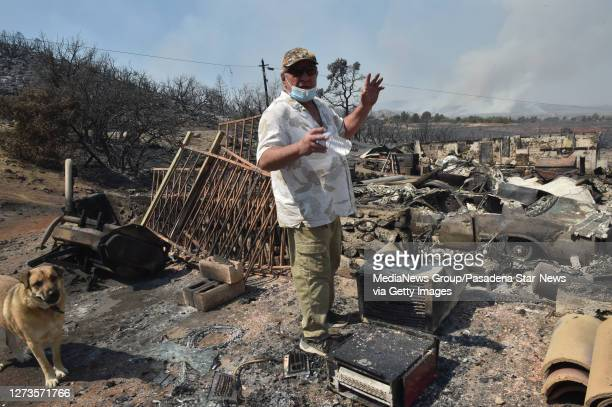 Frank Kenton with his dog Clyde looks over the remains of buildings that burnt during the Bobcat Fire last night in Juniper Hills on Saturday...