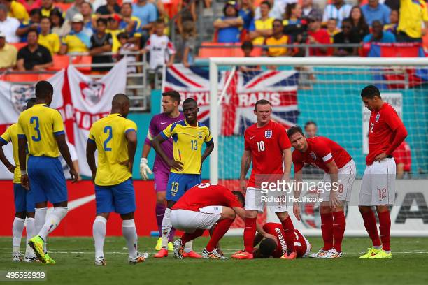 Frank Lampard and Rickie Lambert of England check on injured Alex OxladeChamberlain of England as he goes lies on the pitch during the International...