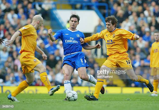 Frank Lampard of Chelsea clashes with Kevin Kilbane and Thomas Gravesen during the FA Barclaycard Premiership match between Chelsea and Everton at...