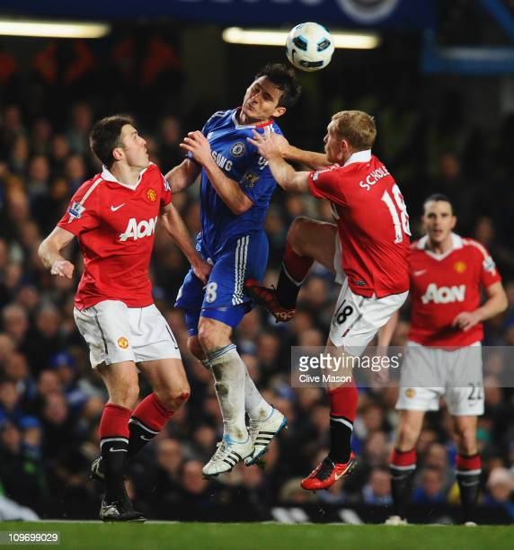 Frank Lampard of Chelsea wins a header against Michael Carrick and Paul Scholes of Manchester United during the Barclays Premier League match between...
