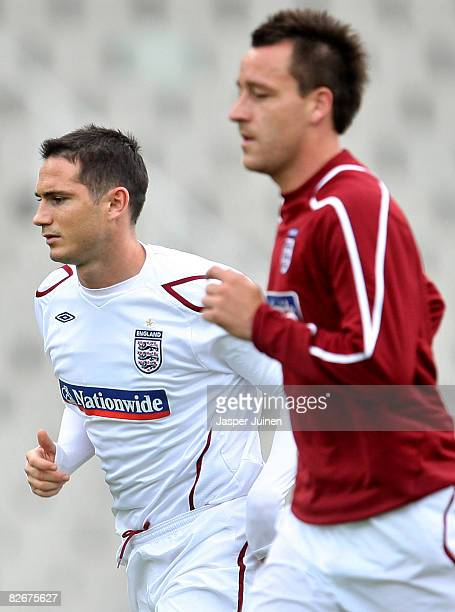 Frank Lampard of England runs flanked by his teammate John Terry during a training session prior to tomorrow's FIFA2010 World Cup Qualifier match...
