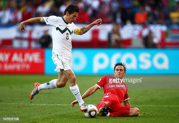 Frank Lampard of England slides in a tackle on Robert Koren of Slovenia during the 2010 FIFA World Cup South Africa Group C match between Slovenia...