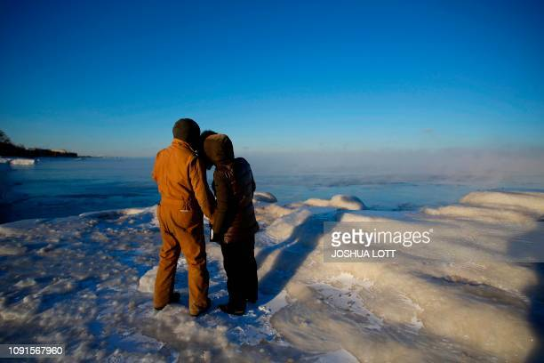 Frank Lettiere and Jelena Miletic view Lake Michigan's frozen shoreline as temperatures dropped to 20 degrees F on January 30 2019 in Chicago...