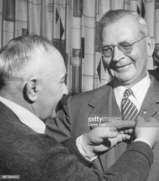 Frank Mallich, left, puts service pin on L. M. Pexton, president of Denver Union Stock Yard Co. Pexton has been with company 41 years, president for...