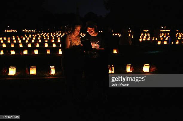 Frank Marron and Colleen Miller stand amidst luminaries marking Civil War graves at the Soldiers' National Cemetery on June 30 2013 in Gettysburg...