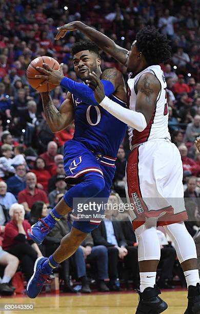 Frank Mason III of the Kansas Jayhawks drives to the basket against Jovan Mooring of the UNLV Rebels during their game at the Thomas Mack Center on...