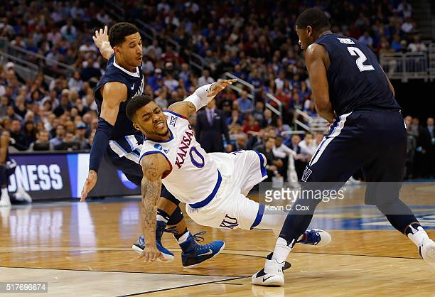 Frank Mason III of the Kansas Jayhawks falls as he drives between Josh Hart of the Villanova Wildcats and Kris Jenkins in the second half during the...