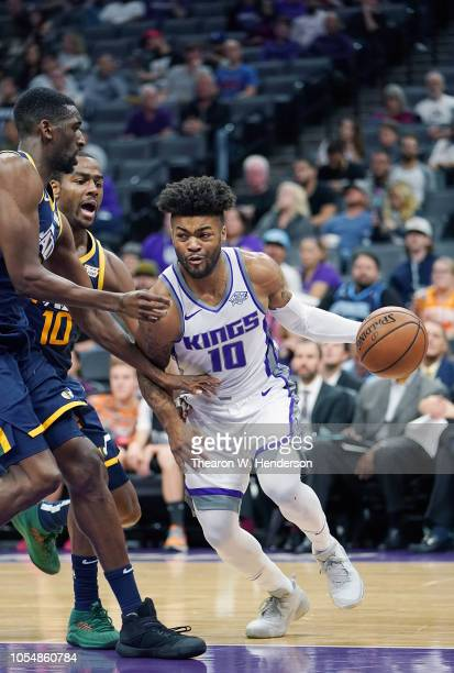 Frank Mason III of the Sacramento Kings drives on Alec Burks and Ekpe Udoh of the Utah Jazz during the second half of their NBA basketball game at...
