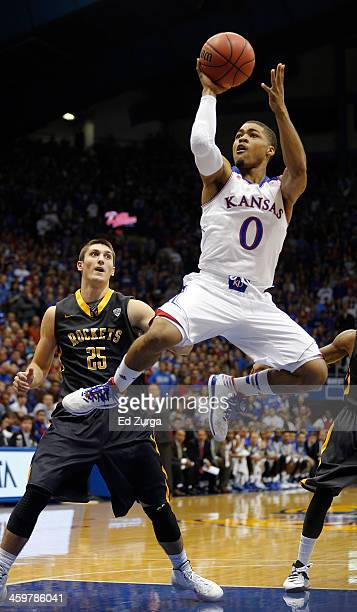 Frank Mason of the Kansas Jayhawks shoots past Jordan Lauf of the Toledo Rockets at Allen Fieldhouse on December 30, 2013 in Lawrence, Kansas.