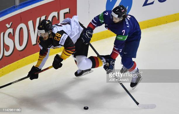 Frank Mauer of Germany and Robert Lachowicz of Great Britain vie for the puck during the group A stage match Germany vs Great Britain of the 2019...