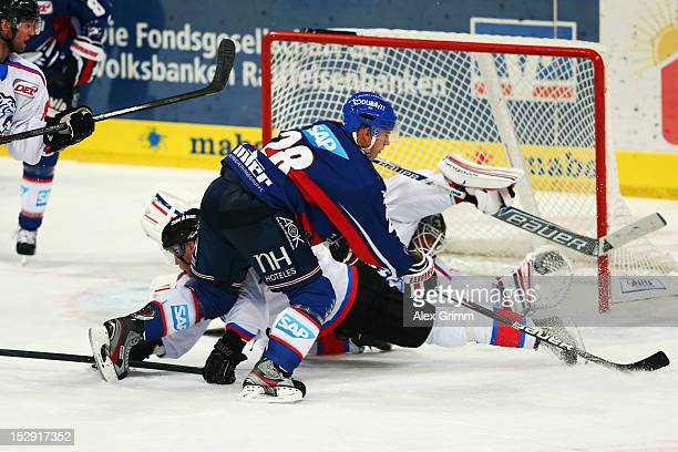 Frank Mauer of Mannheim tries to score against goalkeeper Tyler Weiman and Jame Pollock of Ice Tigers during the DEL match between Adler Mannheim and...