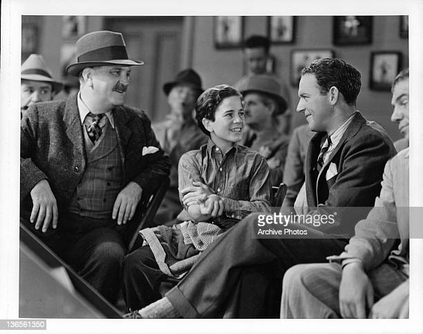 Frank Morgan watches as Gene Reynolds talks to prize fighter William Gargan in a scene from the film 'The Crowd Roars' 1938