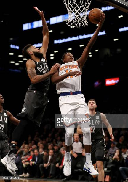 Frank Ntilikina of the New York Knicks heads for the net as Allen Crabbe of the Brooklyn Nets defends at the Barclays Center on December 14 2017 in...