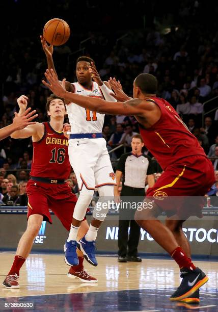 Frank Ntilikina of the New York Knicks passes the ball as Cedi Osman and Channing Frye of the Cleveland Cavaliers defend at Madison Square Garden on...