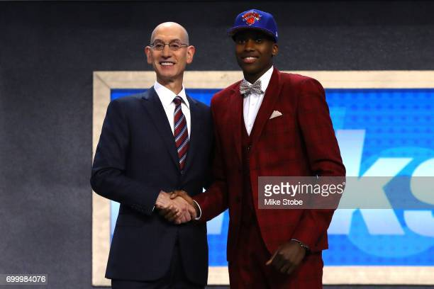 Frank Ntilikina walks on stage with NBA commissioner Adam Silver after being drafted eighth overall by the New York Knicks during the first round of...