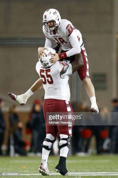 Frank Nutile of the Temple Owls celebrates with Brian Carter after throwing a touchdown against the Cincinnati Bearcats during the second half at...